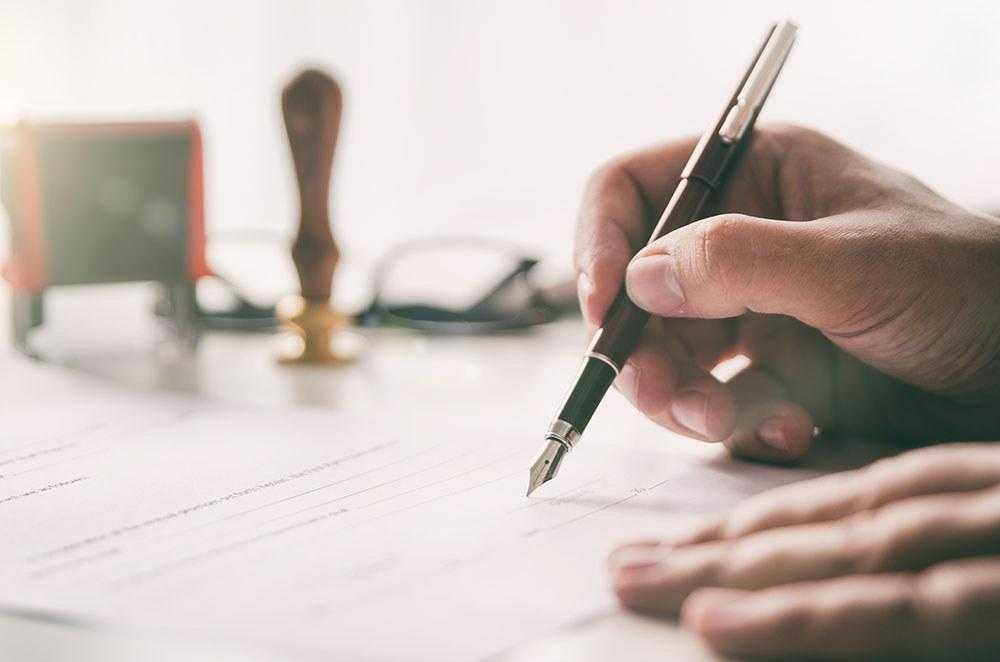 krupni-plan-ruku-koje-potpisuju-dokument
